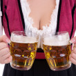 Young sexy oktoberfest woman wearing a dirndl holding two beer m — Foto de Stock