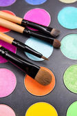 Make-up brushes and colorful eyeshadow palette over black — Stock Photo