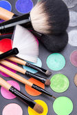 Close up of make-up brushes and colorful eyeshadow palette over — Stock Photo