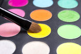 Make-up brush and colorful eyeshadow palette over black close up — Stock Photo