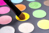 Close up of Make-up brush and colorful eyeshadow palette over bl — Stock Photo