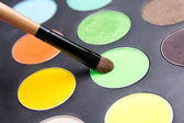 Close up of make-up brush and colorful eyeshadow palette — Stock Photo