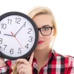 Beautiful teenage girl in eyeglasses holding clock isolated on w — Stock Photo #33345501