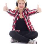 Happy teenage girl listening music in earphones and thumbs up is — Stock Photo #33345569
