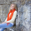 Beautiful woman in warm clothes sitting against stone wall — Stock Photo