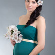 Beautiful pregnant woman in green dress over grey background — Stock Photo