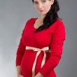 Stock Photo: Beautiful pregnant woman in red dress over grey background
