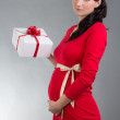 Beautiful pregnant woman in red dress with gift over grey backgr — Stock Photo #33884561
