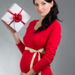 Portrait of beautiful pregnant woman in red dress with gift box — Stock Photo