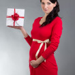 Beautiful pregnant woman in red dress with gift box over grey ba — Stock Photo