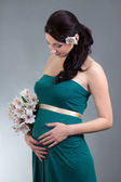 Attractive pregnant woman in green dress with flowers over grey — Stock Photo