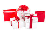 Gift bags and boxes with red ribbon on white background — Stock Photo