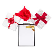 Gift boxes with red ribbon and gift list on white background — Stock Photo