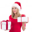 Young blondie woman in santa hat posing with gift boxes isolated — Stock Photo