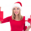 Beautiful young woman in santa hat with gifts isolated on white — Stock Photo