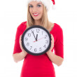 Happy woman in santa hat with clock posing isolated on white — Stock Photo