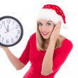 Surprised woman in santa hat with clock posing isolated on white — Photo