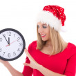 Attractive woman in santa hat with clock posing isolated on whit — Stock Photo
