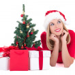 Dreaming woman lying down with christmas tree and gifts isolated — Stock Photo #34589629
