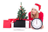 Woman lying down with clock,notebook, christmas tree and gifts — Stock Photo