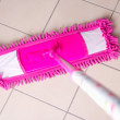 Pink mop cleaning tile floor in bathroom — Stock Photo