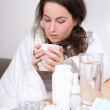 Ill woman drinking tea in her living room — Stockfoto