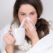 Ill woman with cup of tea and handkerchief — Stockfoto