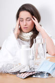 Young attractive woman with headache and table with glass of wat — Stock Photo