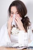 Mujer enferma sonarse la nariz en su sala de estar — Foto de Stock