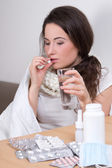 Young ill woman taking pills in her living room — Stock Photo