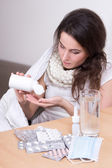 Young attractive ill woman taking pills in her living room — Foto Stock