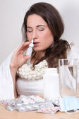 Young woman using nasal spray in her living room — Stock Photo