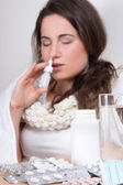 Young sick woman using nasal spray in her living room — Stock Photo