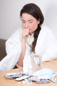 Young woman sneezing and pills on the table — Stock Photo