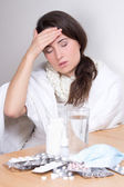 Young woman with headache and pills on the table — Stock Photo
