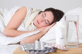 Sick woman sleeping in bed and pills on the table — Stock Photo