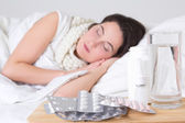 Young sick woman sleeping in bed and pills on the table — Stock Photo