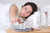 Giovane donna malata a letto e pillole sul tavolo — Foto Stock