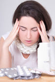 Brunette woman with headache and pills on the table — Stock Photo
