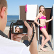 Beautiful woman in changing cabin and photographer on the beach — Stock Photo