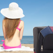 Woman sitting  and suitcase with passports on the beach — Photo