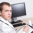 Young male doctor working in office — Stock Photo