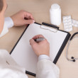 Male doctor prescribing treatment in modern office — Stock Photo