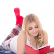Stock Photo: Pretty teenage girl in pajamas lying and reading book isolated o