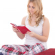 图库照片: Pretty teenage girl in pajamas sitting and reading book isolated