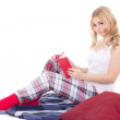 Pretty teenage girl in pajamas sitting with book isolated on whi — Stock Photo