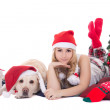 Attractive teenage girl in pajamas lying with dog in santa hat i — Stock Photo #37177303