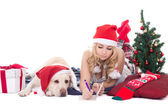 Teenage girl with dog in santa hat and christmas tree isolated o — Stock Photo