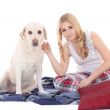 Stock Photo: Young beautiful blond in pajamas with dog isolated on white