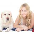 Young beautiful blond in pajamas lying with dog isolated on whit — Stock Photo